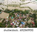 Small photo of Sakonnakhon, Thailand - August 3, 2017 (Ban kang tha lap village,Kusumal district,Sakonnakhon) : Flood waters overtake a house and rice field in northeast of Thailand from above view by drone