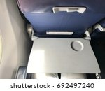 Small photo of Airplane cabin is all white. All its decorations are necessary stuffs and safety. The gray Tray table for passenger in plane.