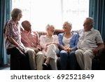 smiling senior friends talking... | Shutterstock . vector #692521849