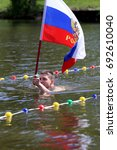 Small photo of Having a swim with the flags on the water. June 2017, Russia, Zavodoukovsk: Opening of the swimming season in the Albatros hardening club.