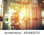 plant growing out of coins with ... | Shutterstock . vector #692683270