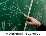 Hand of a student pointing at green chalkboard with normal distribution on it - stock photo