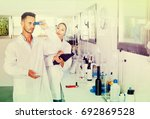 Small photo of Two young diligent researchers in white coat checking wine acidity and sugar saturation in chemical laboratory