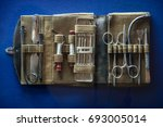 Small photo of Aged nurse physician accessory in container on blue background. Aseptic hemostat, hypodermic tube, extraction tenaculum, steel hand lancet, tooth probe device, iron forcipes. Closeup obsolete object
