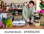 Small photo of Male attractive florist accepting orders over a phone and withdrawing money from a credit card in a flower shop. Floral design studio, making decorations. Flowers delivery service.