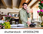 Small photo of Male attractive florist accepting orders over a phone and withdrawing money from a credit card in a flower shop. Floral design studio, making decorations. Flower delivery service.