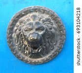 Small photo of Ancient bronze lion's head door accent on a blue background