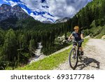 mountain biking woman along...   Shutterstock . vector #693177784