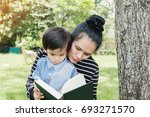 mother and boy sit under a tree ... | Shutterstock . vector #693271570