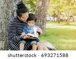 mother and boy sit under a tree ... | Shutterstock . vector #693271588