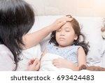 mother measuring temperature of ...   Shutterstock . vector #693424483