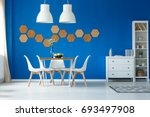 Small photo of Modern living room with open spacious dining area accented with royal blue walls and simple furniture