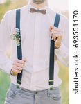 Small photo of The close-up outlook of the groom in the white shirt, gray pants, suspenders with the flower accessories and wooden butterfly on hir neck in the green wood.