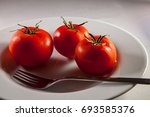 three tomatoes in a bowl with a ... | Shutterstock . vector #693585376