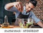 man adding salt into fresh salad | Shutterstock . vector #693608269