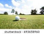golf ball near hole  background ... | Shutterstock . vector #693658960