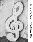 Treble clef on wall background. ...