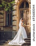 beautiful bride near old big... | Shutterstock . vector #693680044