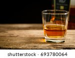 whiskey on rustic wood table. | Shutterstock . vector #693780064