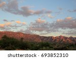 Small photo of Pretty rippled pink and gray monsoon clouds spread out over the glowing red sunset Catalina mountains in the Tucson Arizona desert