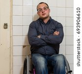 Small photo of Disabled paraplegic young man in shirt and jeans sitting in a wheelchair with strong minus glasses