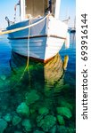 Small photo of Fishing boat are moored in the clear water. Milos island. Adamas port. Greece.