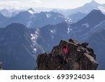 Female Hiker Climbing A Boulde...