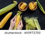 woman's hands clean corn cob.... | Shutterstock . vector #693972703