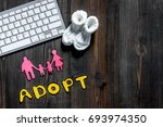Small photo of Adopt word, paper silhouette of family and booties near keyboard on dark wooden table background top view copyspace