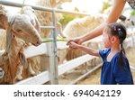 cute little girl feeding sheeps ...   Shutterstock . vector #694042129
