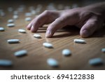 Small photo of Drug addict with withdrawal symptoms lying on floor. Drug addiction, medical abuse and narcotics hook and dependence concept. Tablet overdose. Depression and problem. Hand surrounded by many pills.