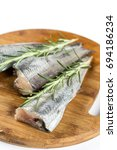 Small photo of Fresh raw hake fish with rosemary branches.