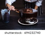 glazing chocolate mousse cake ... | Shutterstock . vector #694232740