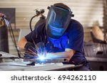 male in face mask welds with... | Shutterstock . vector #694262110