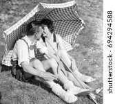 Small photo of Couple showing affection while sitting under umbrella