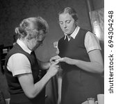 Small photo of Woman applying adhesive bandage to finger of another