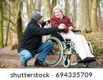 caregiver man walking with... | Shutterstock . vector #694335709