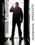 Small photo of Man standing at doorway threshold, in silhouette with flashlight creating glare