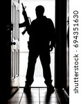 Small photo of Intruder standing at doorway threshold, in silhouette with AR-15 style long gun