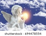 a small figure of ceramic angel ... | Shutterstock . vector #694478554