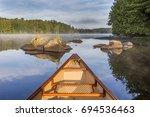 bow of canoe on a lake in early ... | Shutterstock . vector #694536463
