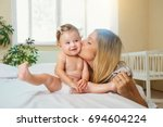mother and baby in a diaper... | Shutterstock . vector #694604224