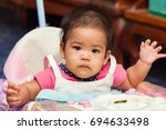 little child smears food while... | Shutterstock . vector #694633498