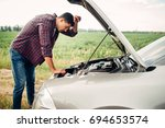 tired man tries to repair a... | Shutterstock . vector #694653574