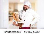 young baker holding some bread... | Shutterstock . vector #694675630
