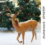 deer statue in snow in front of christmas trees - stock photo