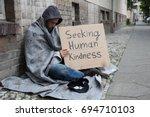 Male Beggar In Hood Showing...