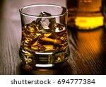 glass of whiskey on the rocks... | Shutterstock . vector #694777384