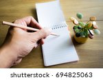 Small photo of Man left hand with pencil writing on notebook