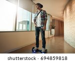 Small photo of Indoor shot of young man riding on self-balancing electric scooter in office. Creative professional on hover board.
